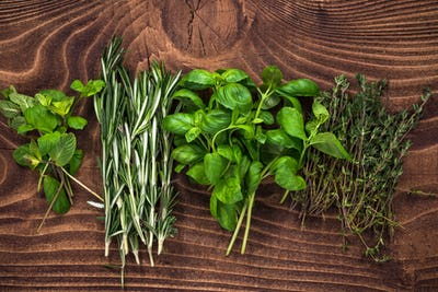 Fresh organic herbs collection on wooden table