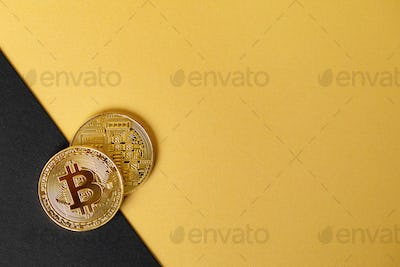 Gold bitcoin cryptocurrency coins on split gold yellow and black backgound