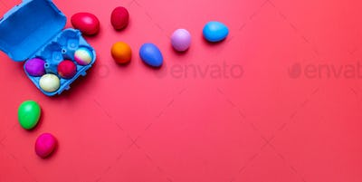Easter eggs, pastel colors painted and a carton case, orange color background