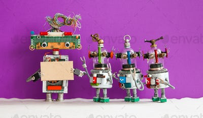 Robot with a cardboard mockup and four funny robotic toys on purple wall background.