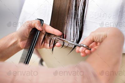 Cutting ends of long brown hair in close-up