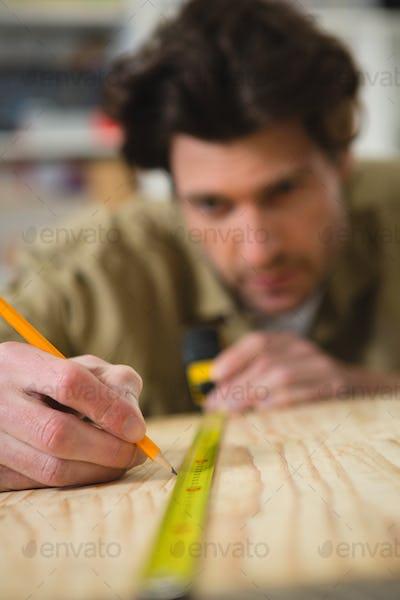 Male carpenter measuring and marking wood in workshop