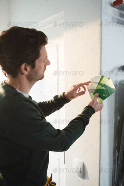 Male carpenter checking colour shade of wall in workshop
