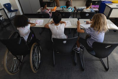Disable schoolgirl with classmates studying in classroom