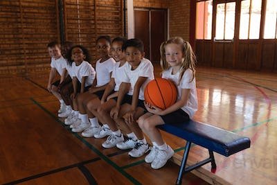 Side view of schoolkids with basketball sitting on bench looking at camera in basketball court