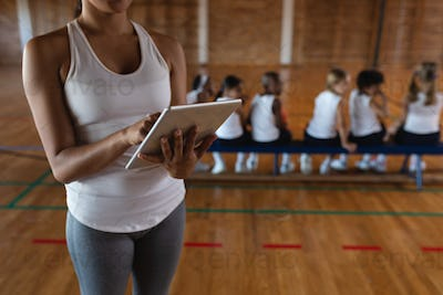 Mid section female basketball coach using digital tablet at basketball court in school