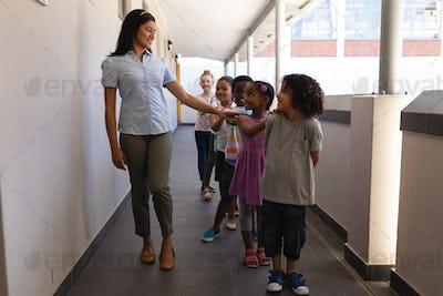 Schoolkids with teacher standing in row in hallway