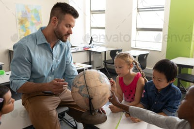 Male teacher teaching his kids about geography in classroom