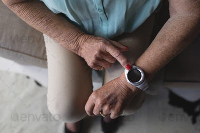 Close-up view of senior woman checking time on her wristwatch at home