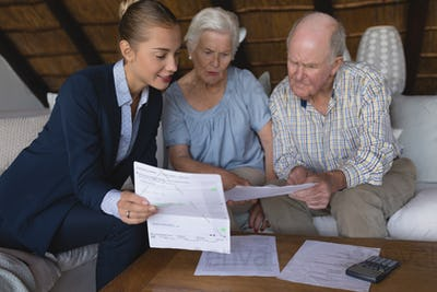 Female doctor and senior couple discussing over medical reports at home