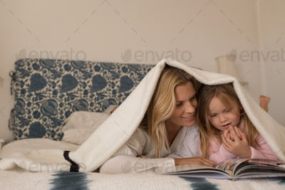 Happy mother reading a book with her daughter under blanket in bedroom