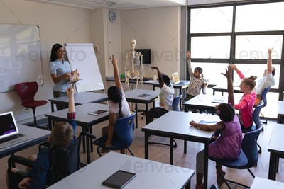 Side view of schoolkids raising hands while sitting at desk in classroom of elementary school