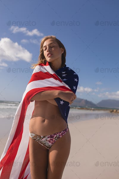 Portrait of young woman wrapped in American flag at beach on a sunny day