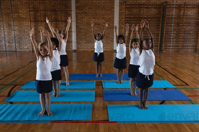 Front view of schoolkids doing yoga on a yoga mat in school