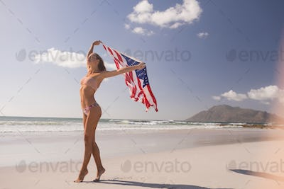 Young woman holding waving American flag at beach on a sunny day