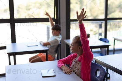 Side view of school kids raising their  hand while sitting at desk in classroom of elementary school