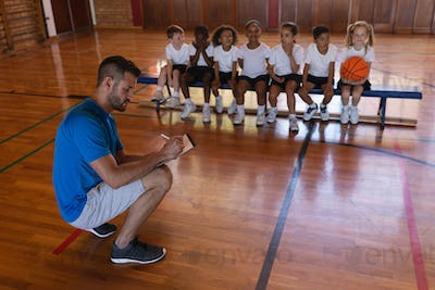 Basketball coach writing on clipboard and schoolkids sitting on bench at basketball court in school