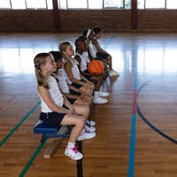 Side view of schoolkids sitting on bench at basketball court in school