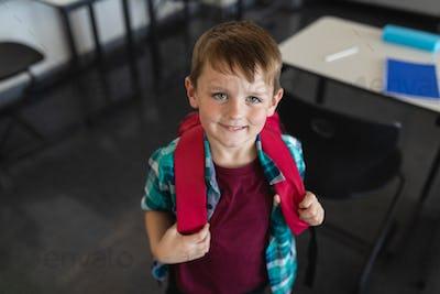 Happy schoolboy looking at camera in classroom