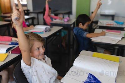 Side view of school kids raising hand in classroom