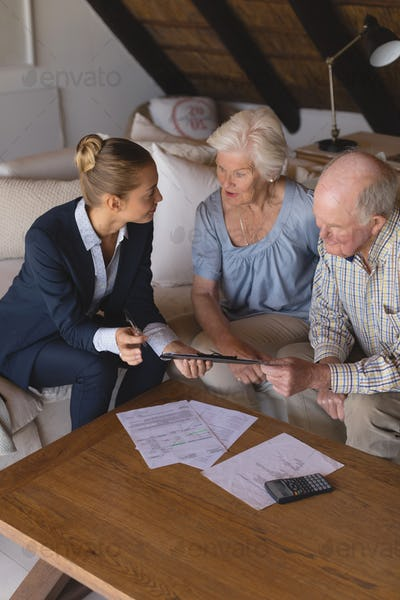 Female doctor and senior couple discussing over clipboard at home