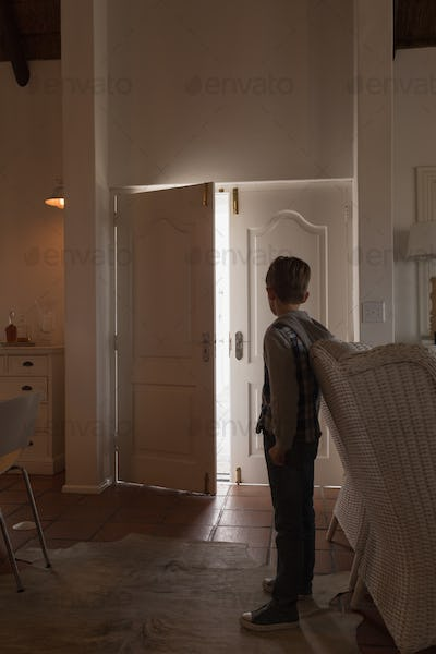 Young boy standing living room and looking thought opened door