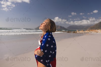 Side view of young woman wrapped in American flag at beach on a sunny day