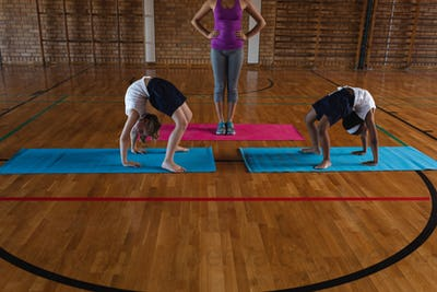 Front view of young female yoga teacher and schoolkids doing yoga on a yoga mat in school