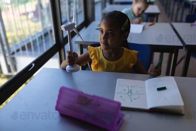 Schoolgirl holding a windmill model at desk in classroom