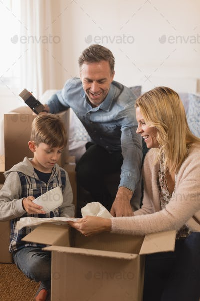 Side view of happy family spending time together while unpacking cardboard boxes in their new home