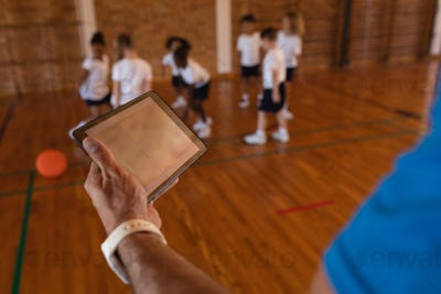 Close-up of basketball coach using digital tablet at basketball court in school