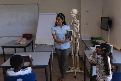 Female teacher teaching schoolboy on digital tablet in classroom