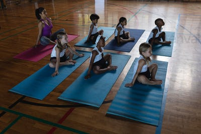 Female yoga teacher and schoolkids doing yoga in school