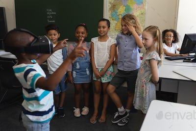 Schoolboy using virtual reality headset in classroom of elementary school