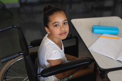 Disabled schoolgirl looking at camera and sitting at desk in classroom of school