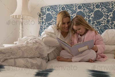 Front view of happy mother with her daughter reading storybook in bedroom at home