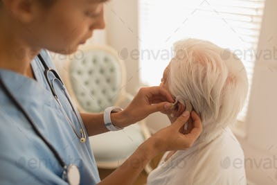 Female physician inserting hearing aid on senior womans ear at home
