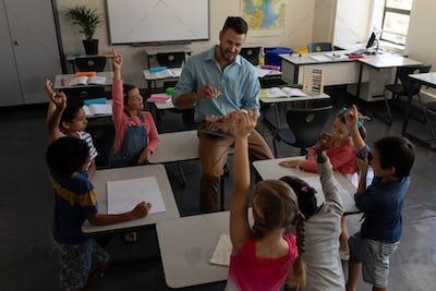 School kids raising hands while teacher studying in classroom of elementary school