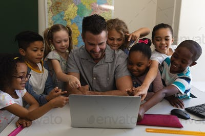 Teacher teaching on laptop and all schoolkids participate in classroom of elementary school