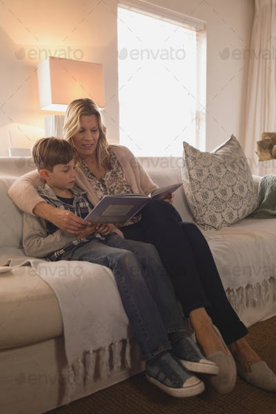 Mother with her son spending time together while reading story book in living room at home