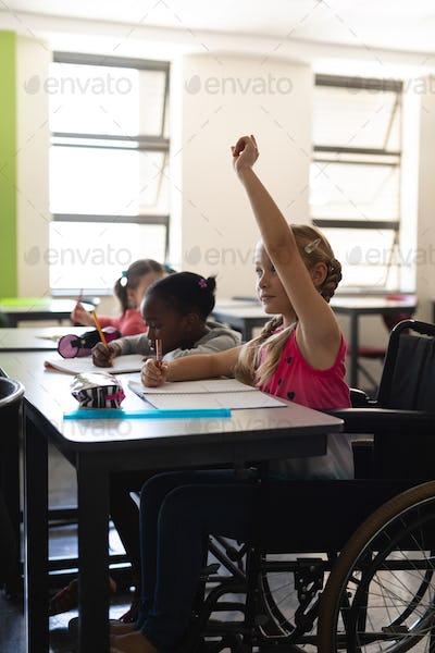 Side view of disable schoolgirl raising hand in classroom of elementary school