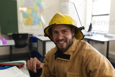 Male firefighter with helmet looking at camera in classroom of elementary school