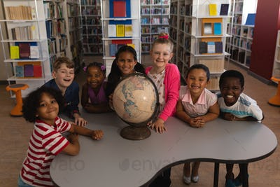 Front view of happy schoolkids with globe looking at camera in school library