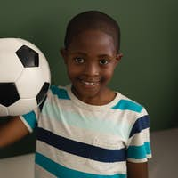 Schoolboy holding football and looking at camera in classroom of elementary school