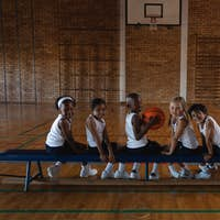 Side view of schoolkids looking at camera while sitting on bench at basketball court in school