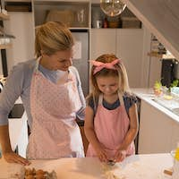 Cute daughter using cookie cutter while loving mother looking at her in kitchen at home