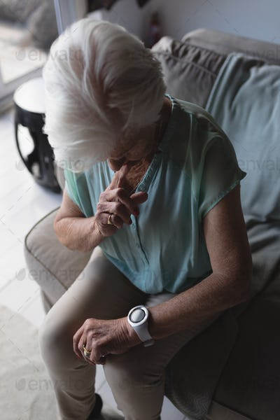 High angle view of a senior woman checking time on her wristwatch at home