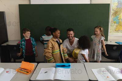 Male firefighter teaching schoolkids about fire safety in classroom of elementary school