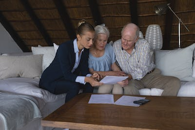 Female doctor and senior couple looking and discussing over medical reports at home