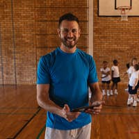 Front view of happy basketball coach using digital tablet at basketball court in school